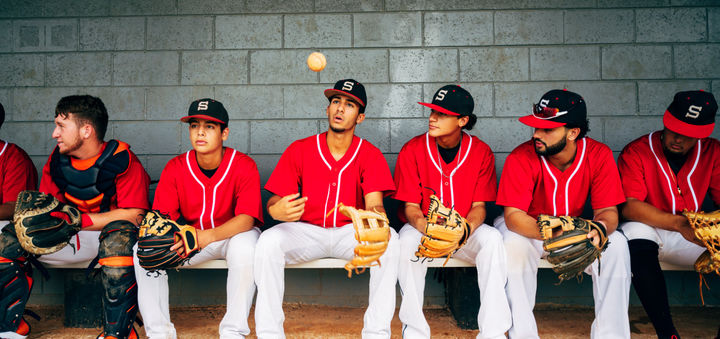 Confident young Hispanic baseball players sitting in dugout